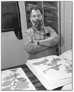 Black and white photograph of Les Mehrhoff with herbarium specimens